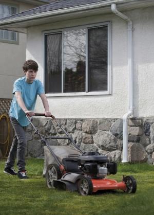 adolescent tondant la pelouse
