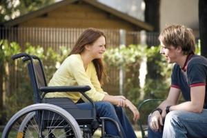 jeune fille en fauteuil roulant souriant à un garçon